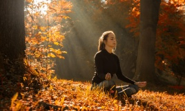 A young woman make yoga position at sunrise. in the autumn fores